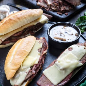 close up Cheesy Mushroom French Dip Sandwiches and a cup of gravy on a large serving plate