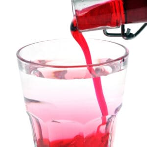 adding pomegranate juice mixed on a glass with sugar and water for homemade grenadine