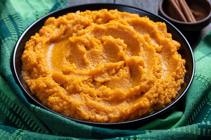 close up Mashed Sweet Potatoes in a medium serving plate, green tablecloth and cinnamon sticks on its background