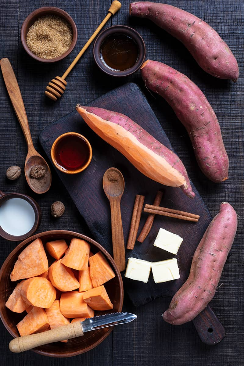 Mashed Sweet Potatoes ingredients in a wooden cutting board and dark wood background