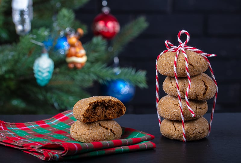 Christmas tablecloth underneath Molasses Cookies, stack of Molasses Cookies with red and white ribbon beside, Christmas tree decor on background