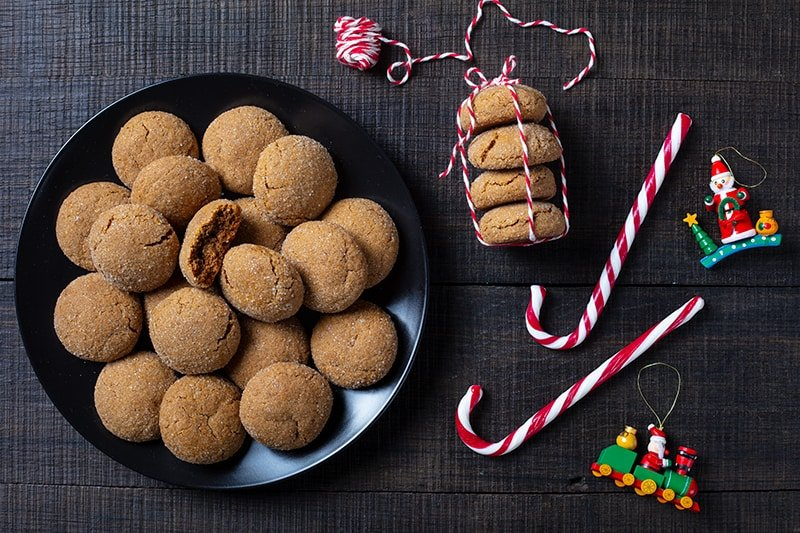 plate with Molasses Cookies, stack of Molasses Cookies tied with red and white ribbon, Christmas candy bars on side