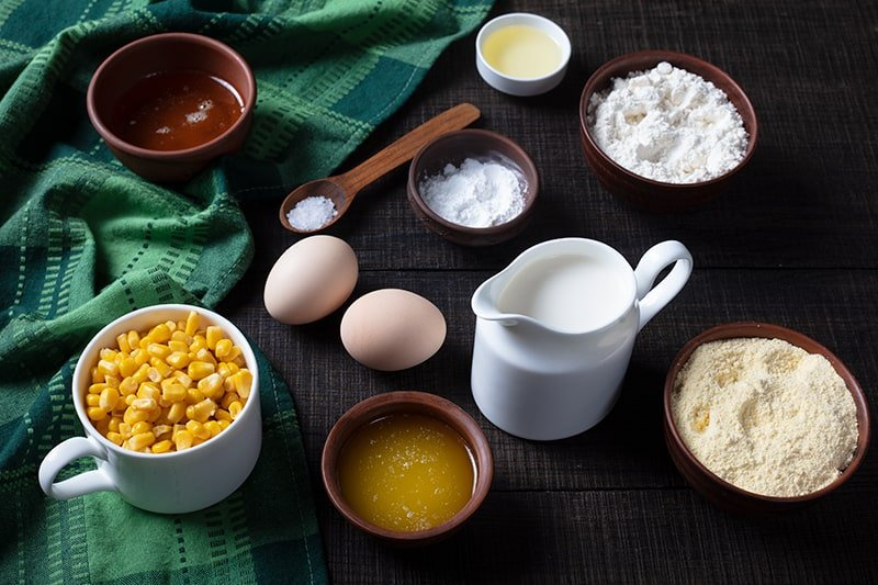 ingredients of Sweet Honey Skillet Cornbread in green tablecloth and wood background