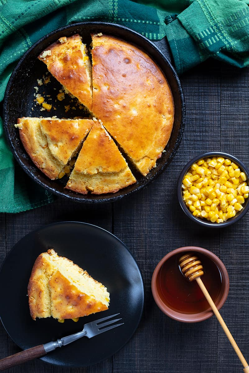 Sweet Honey Skillet Cornbread cut into pie shape wedges, a slice in a black dessert plate, corn kernels and honey in a sauce platter