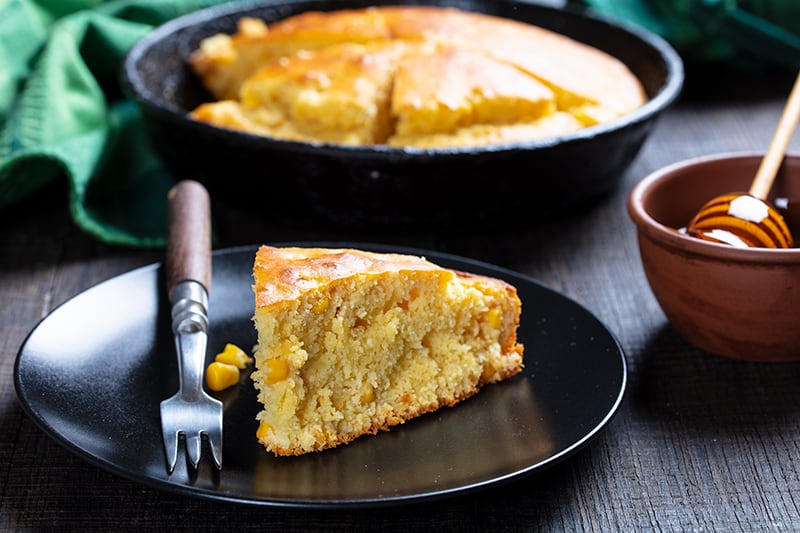 a slice of Sweet Honey Skillet Cornbread on black dessert plate with fork, whole skillet cornbread and honey on background