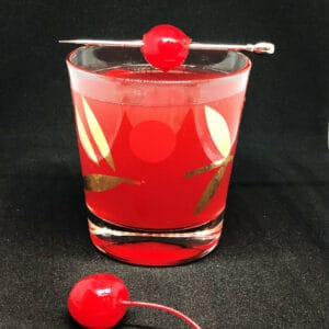 Scofflaw Cocktail on a vintage cocktail glass garnish with a stemmed maraschino cherry