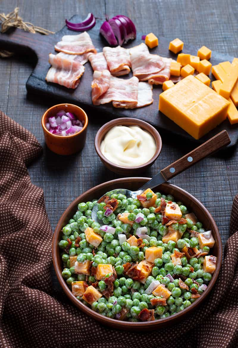 brown polka dot tablecloth underneath a bowl of Cheddar Bacon Green Pea Salad with a spoon, ingredients on wooden chopping board and wood background