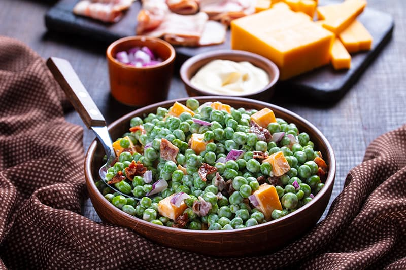 brown polka dot tablecloth underneath a bowl of Cheddar Bacon Green Pea Salad with a spoon on it, ingredients on its background