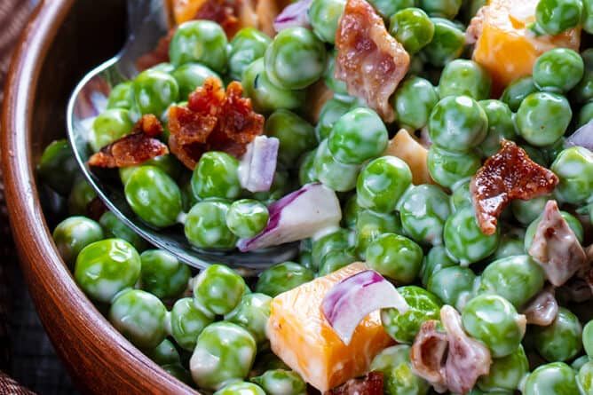 close up brown polka dot tablecloth underneath a bowl of Cheddar Bacon Green Pea Salad with a spoon
