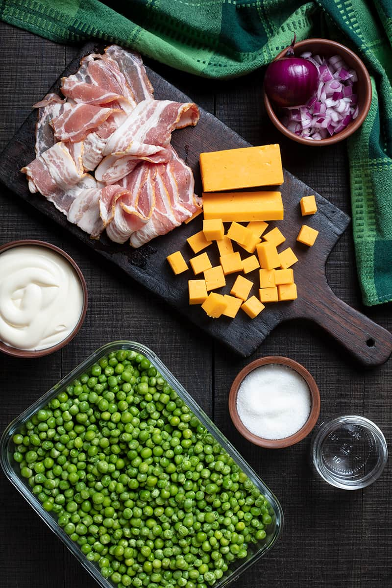 cheddar bacon green pea salad ingredients on wooden chopping board and green tablecloth at one side