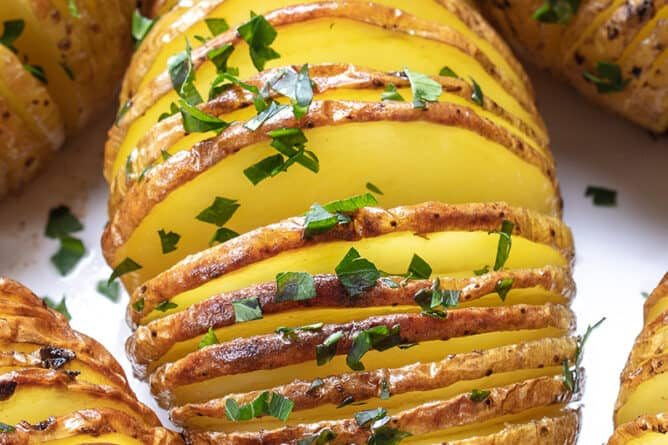 close up Hasselback Potatoes sprinkled with parsley flakes