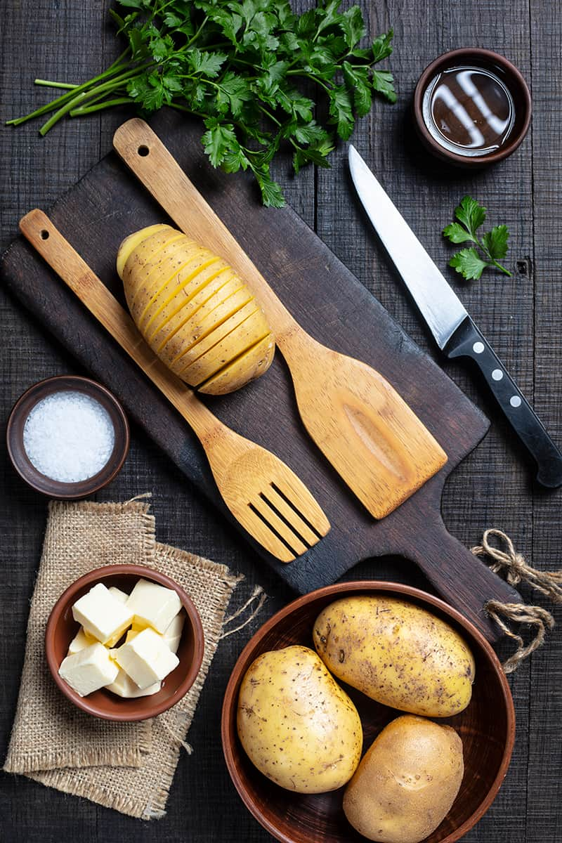 Hasselback Potato Ingredient Spread, cut potato in between wooden spoon on a wooden chopping board