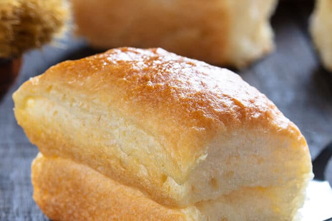 close up piece of soft buttery delicious Parker House Rolls on a wooden background