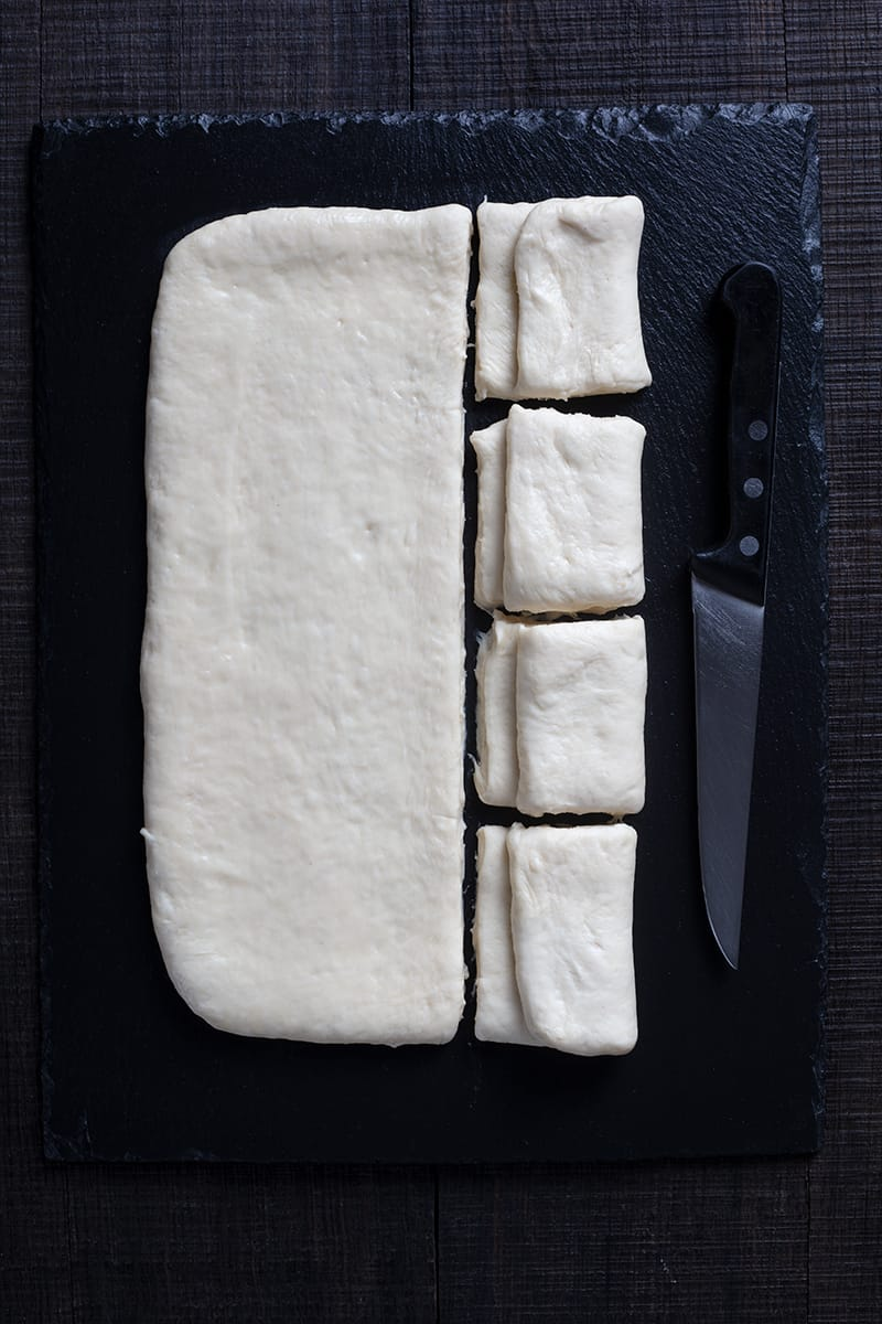 folded and sliced dough for Parker House rolls, small knife beside it