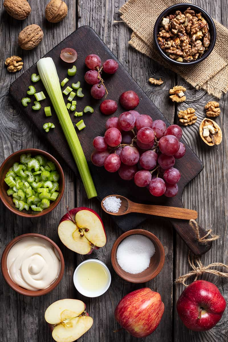 Classic Waldorf Salad ingredients on wood background