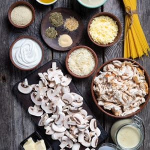Ingredients are mise on place for making chicken tetrazzini on a wood background