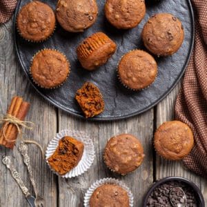 double chocolate pumpkin muffins, cinnamon sticks and chocolate chips on wooden background with polka dot brown tablecloth