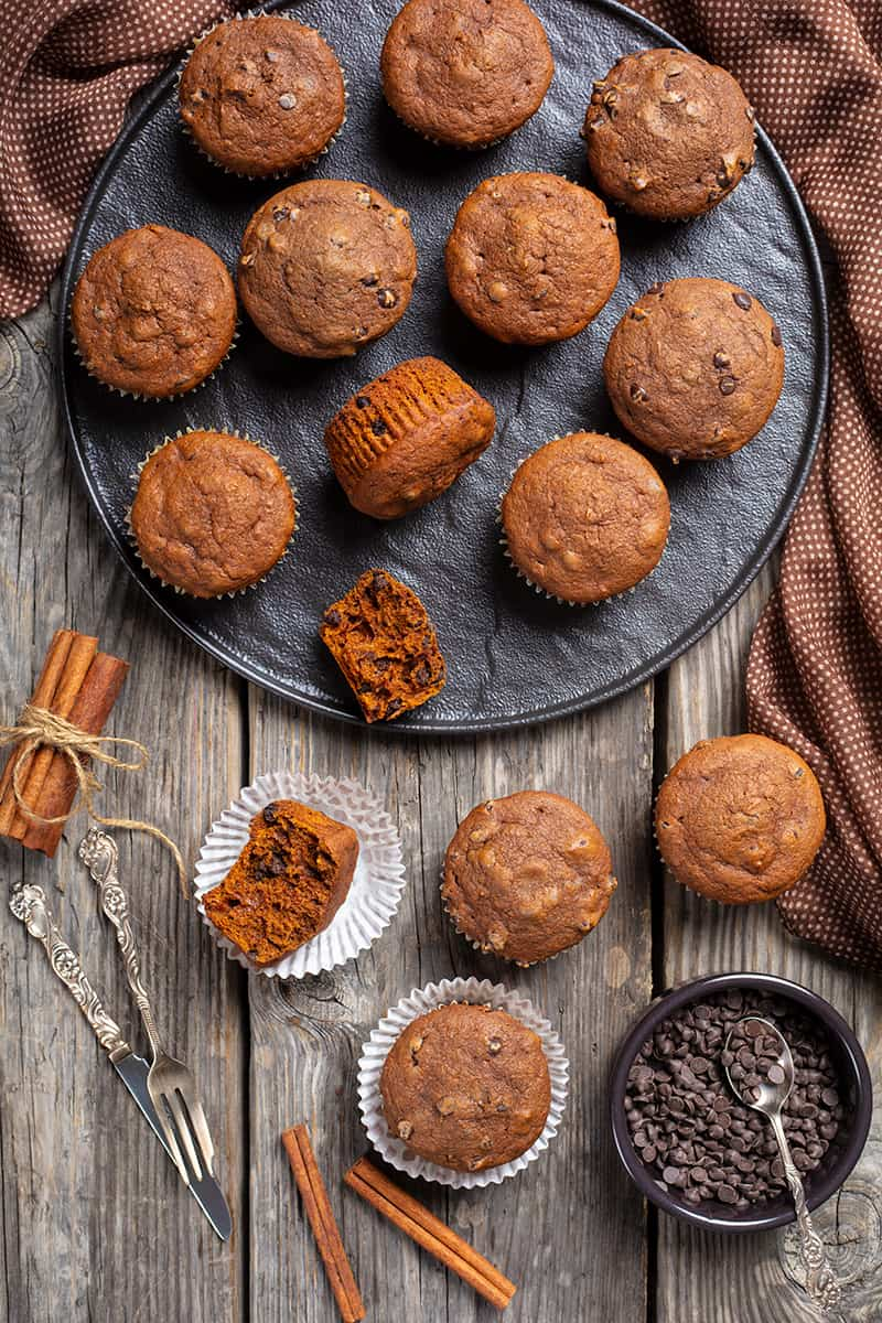 close up double chocolate pumpkin muffins, cinnamon sticks and chocolate chips on wooden background with polka dot brown tablecloth