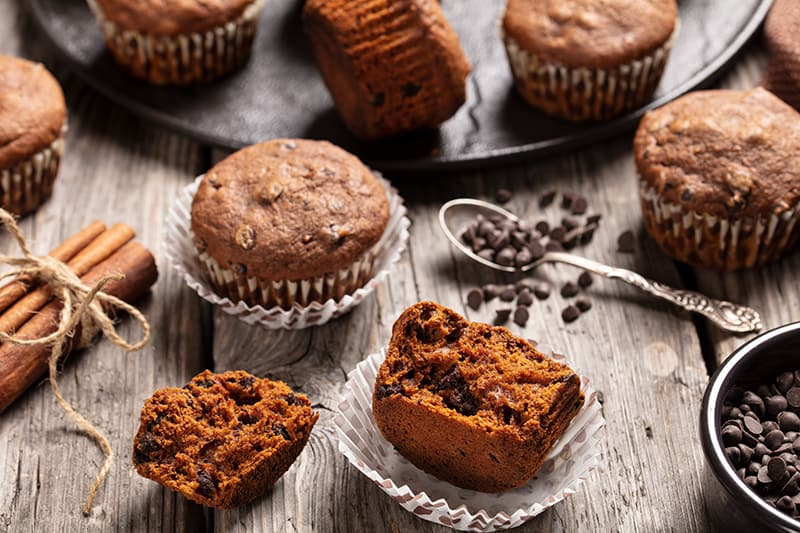 close up double chocolate pumpkin muffins on polka dot liner, cinnamon sticks and chocolate chips
