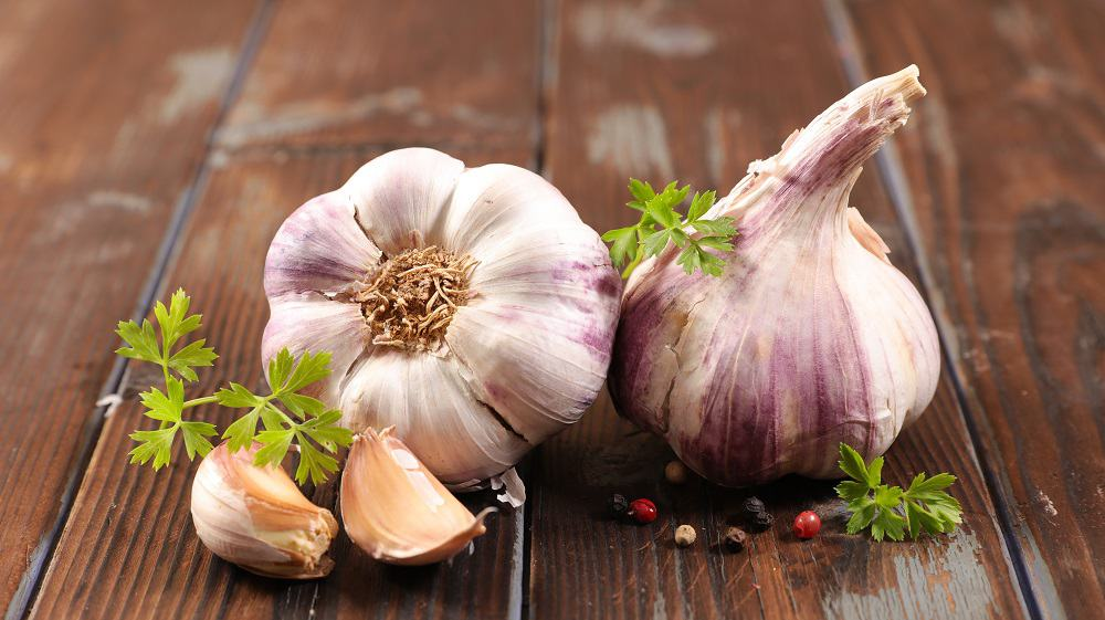 garlic clove and bulb on wood background with some parsley leaves