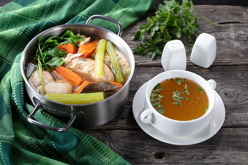a green table cloth and boiling pan with Chicken broth made with vegetables and chicken breast , white soup bowl in a plate filled with chicken broth, salt and pepper shakers beside it