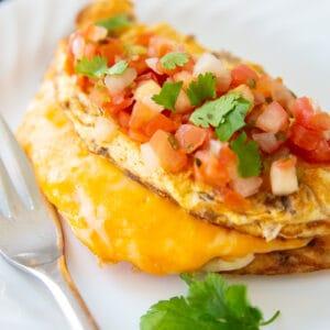 Taco Omelette top with pico de gallo and cilantro on a white plate with fork