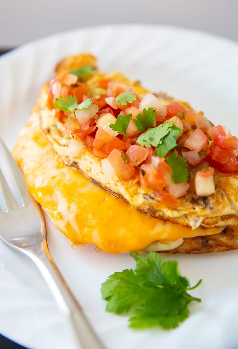 close up Taco Omelette top with pico de gallo and cilantro on a white plate with fork