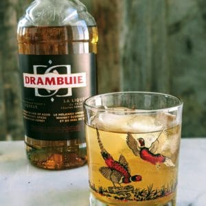 Rusty Nail cocktail on a pheasant glass with a bottle of Drambuie behind it