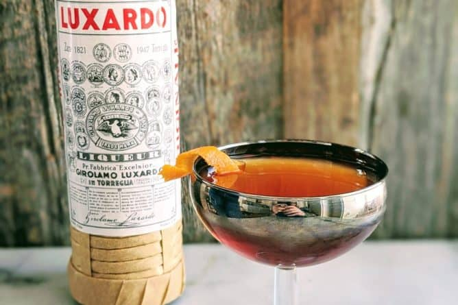 Martinez Cocktail in a silver coupe glass with a bottle of Luxardo behind it