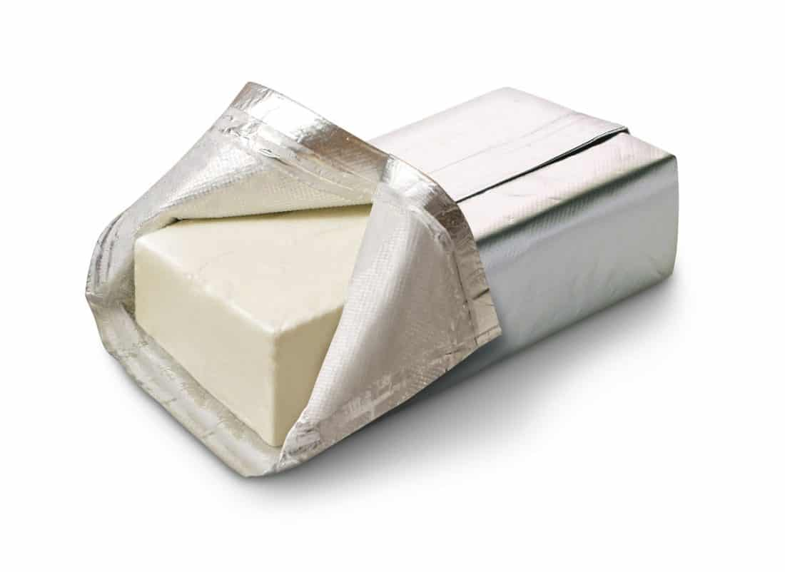whole cream cheese wrapped in a foil wrapper with one side opened