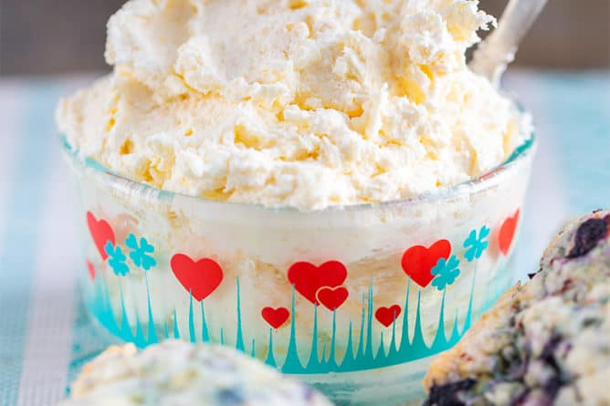 clotted cream in a heart patterned Pyrex container and blueberry scones