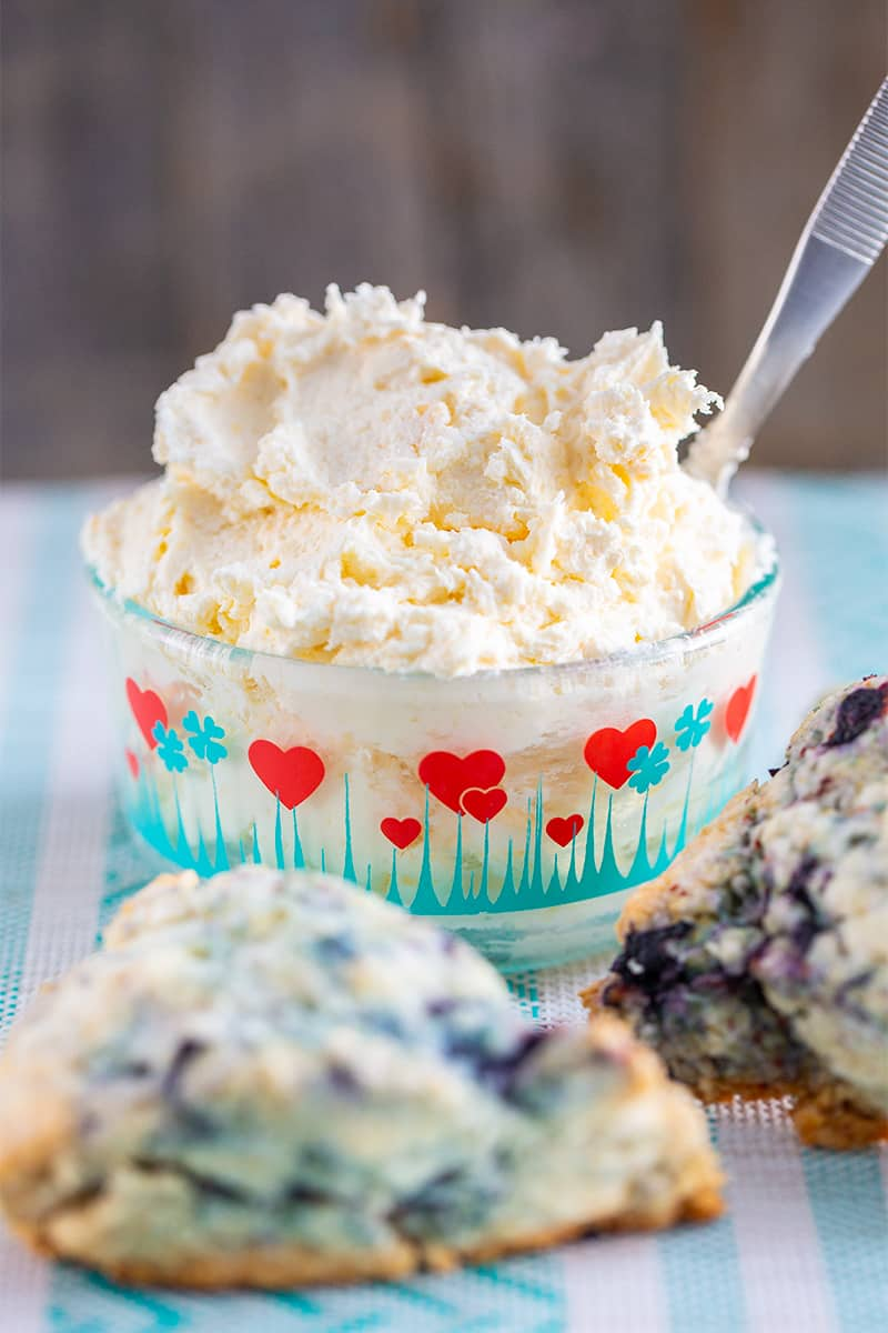 close up clotted cream in a heart patterned Pyrex container and blueberry scones