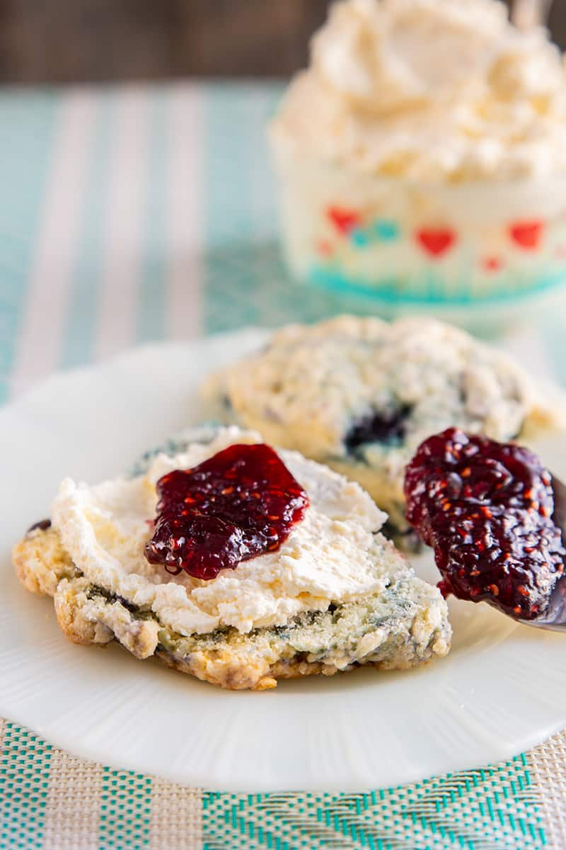 white plate with clotted cream on a scone topped with some jam, underneath is a pink and blue printed table cloth, clotted cream in a heart patterned Pyrex container in background