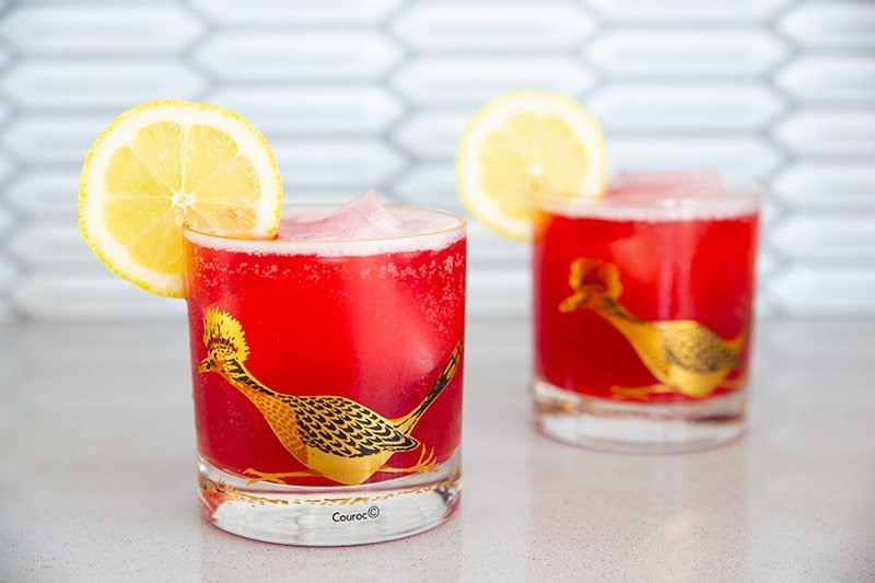 Cranberry Whiskey Sour in a vintage roadrunner decorated glasses garnished with lemon