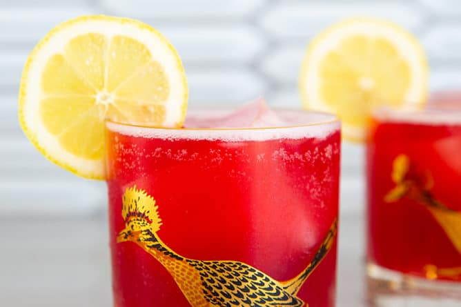 Cranberry Whiskey Sour in a vintage roadrunner decorated glass garnished with lemon