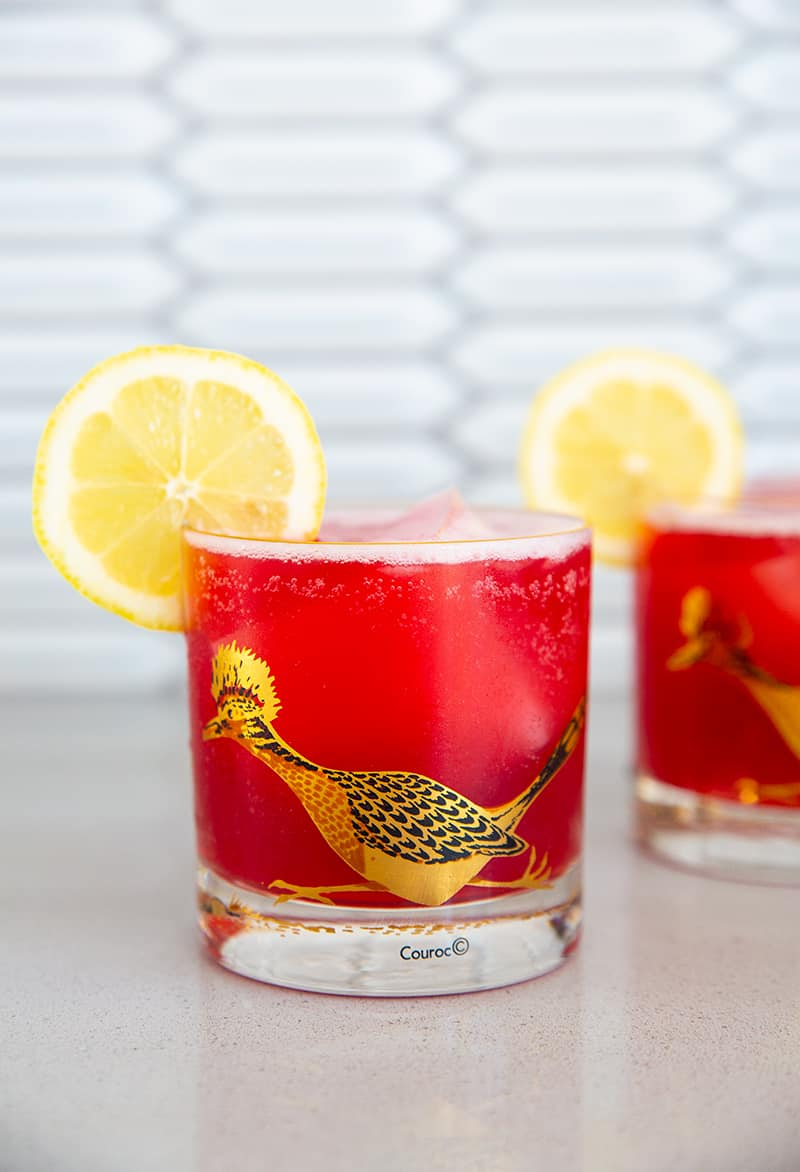 close up cranberry whiskey sour in a vintage roadrunner decorated glass garnished with lemon