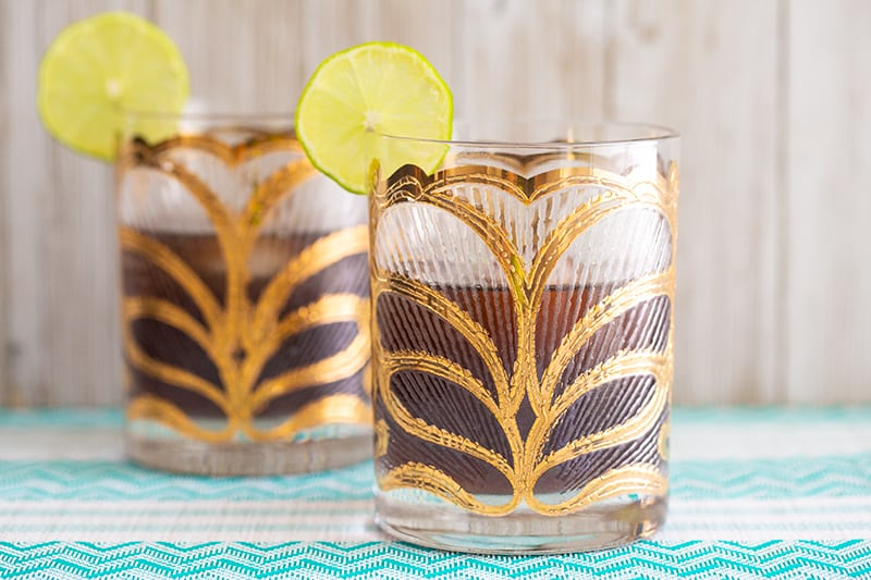Cuba Libre cocktail garnished with a lime slice, in a glass beautifully gilded in gold