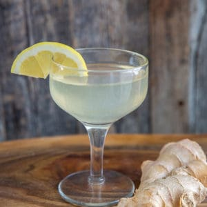 ginger martini in a coupe glass, garnished with a lemon wedge and ginger root beside it