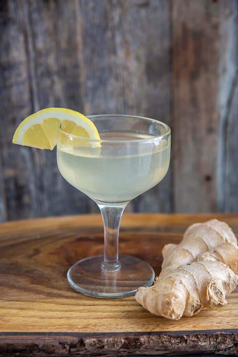 close up ginger martini in a coupe glass, garnished with a lemon wedge and ginger root beside it