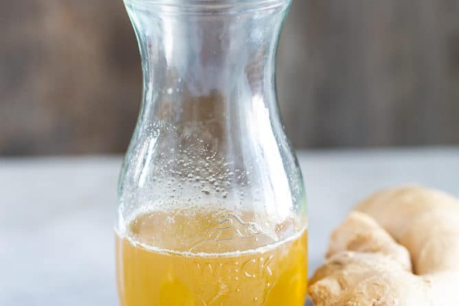 Ginger Simple Syrup in an airtight transparent glass with chuck of ginger beside it and a spoon of honey