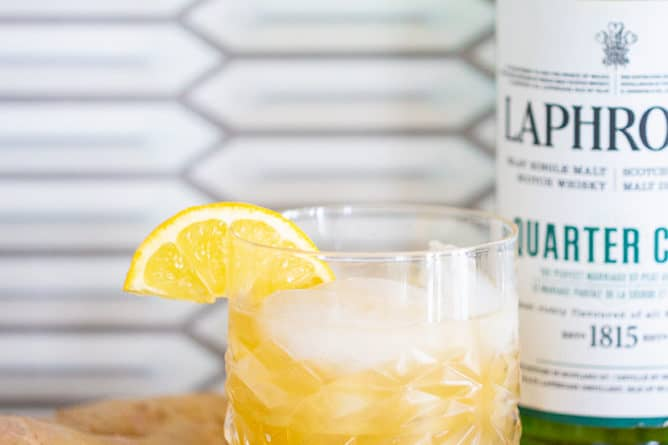 a glass of penicillin cocktail garnished with a lemon slice, a piece of ginger and a bottle of laphroaig
