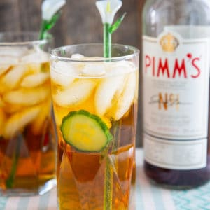 Pimm's cup cocktail in a tall glass with cucumber, and a glass lily flower stir stick.Bottle of Pimm's in background.