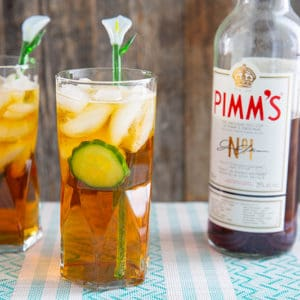 Two Pimm's cup cocktails in a tall glass with cucumber, and a glass lily flower stir stick.Bottle of Pimm's in background.