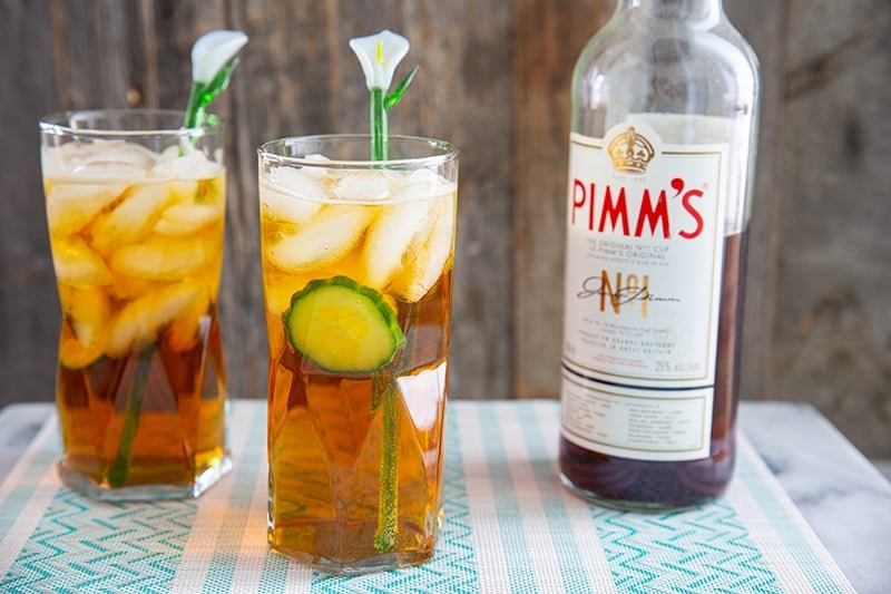 Pimm's cup cocktails in tall glasses with cucumber and a glass lily flower stir stick. Bottle of Pimm's in background.