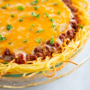 close up of baked spaghetti pie with melted cheese on top and garnished with fresh parsley
