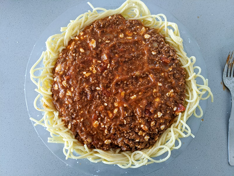 pasta crust with meat sauce on a large Pyrex plate