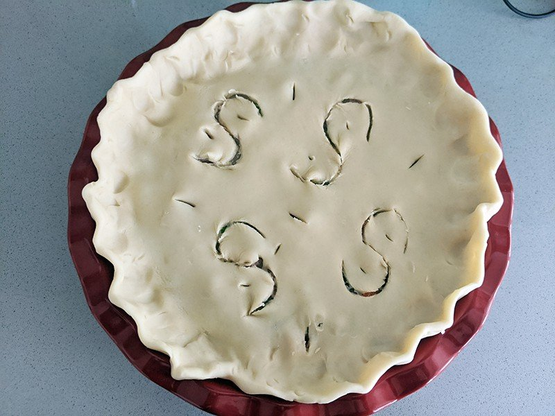 beef and vegetable filling encased with two crust pot pie in a red pie plate