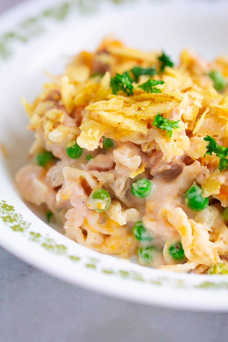 close up tuna casserole in a large white plate, with green peas and potato chips topping
