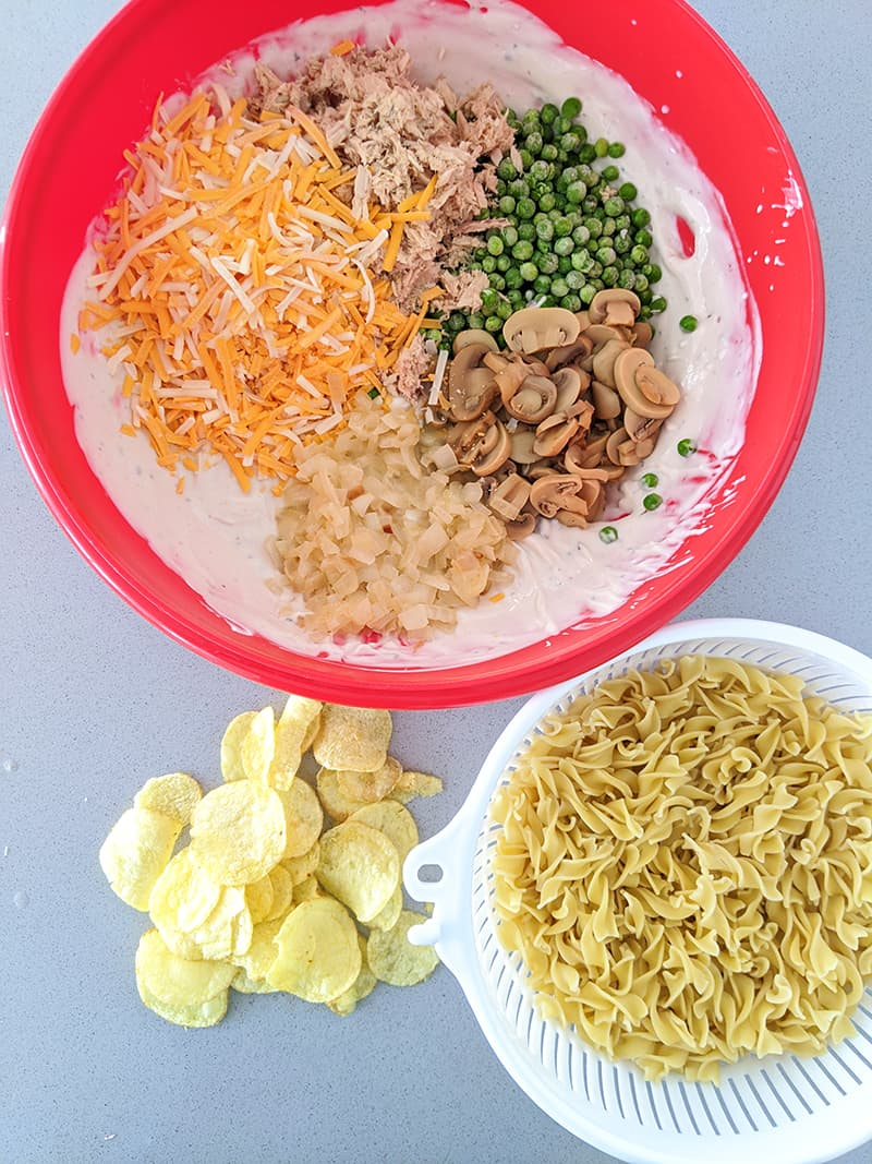 tuna casserole ingredients in a red Pyrex casserole egg noodles in a white strainer potato chips at the side