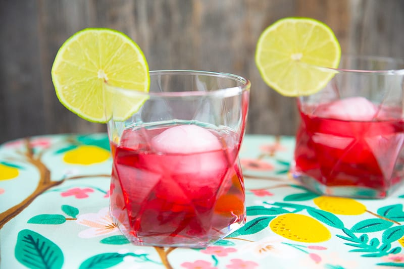 two glasses of woo woo cocktail, cranberry red drinks in clear glasses garnished with lime